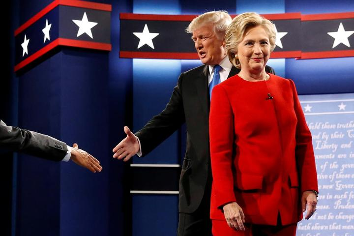 Trump and Clinton greet one another as they take the stage for their first...