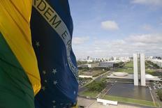 Una bandera de Brasil con el edificio del Congreso Nacional en el fondo, en Brasilia. 19 de noviembre de 2014. Las perspectivas para la economía de Brasil están mejorando luego de atravesar una profunda recesión, aunque la recuperación de la actividad será cuesta arriba y el país tardará en ver avances en la disponibilidad de crédito, dijo el martes la agencia de calificación Moody's. REUTERS / Ueslei Marcelino