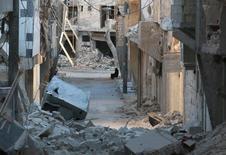 Женщина сидит среди разрушенных зданий в пригороде Алеппо. Больница, расположенная в подконтрольной повстанцам восточной части Алеппо, подверглась авиаударам в среду рано утром и в результате приостановила работу, сообщили врачи. REUTERS/Abdalrhman Ismail