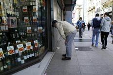 Una persona mira los precios de los productos desde fuera de una tienda en el centro de Santiago. 26 de agosto de 2016. Los operadores financieros en Chile elevaron su estimación de la inflación de septiembre a un 0,6 por ciento, pero mantuvieron sus perspectivas de largo plazo en el centro del rango proyectado por el Banco Central, mostró el miércoles un sondeo del organismo. REUTERS/Ivan Alvarado