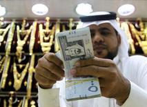 Саудовец пересчитывает деньги в ювелирной лавке в Эр-Рияде 27 сентября 2016 года.  Члены ОПЕК не пришли к соглашению в Алжире, но еще могут договориться в этом году о сокращении нефтедобычи ради поддержки цен, так как экономические трудности вынуждают безусловного лидера картеля Саудовскую Аравию пойти на уступки Тегерану. REUTERS/Faisal Al Nasser