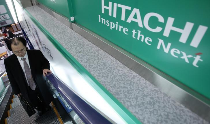 A shopper rides an escalator past a logo of Hitachi Corp at an electronics retail store in Tokyo February 3, 2014. REUTERS/Yuya Shino/Files