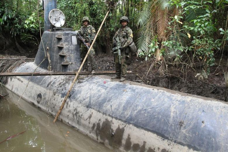 Members of the Colombian Navy stand guard on top of a seized submarine built by drug smugglers in a makeshift shipyard in Timbiqui, department of Cauca February 14, 2011. Colombian authorities said the submersible craft was to be used to transport 8 tons of cocaine illegally into Mexico. REUTERS/Jaime Saldarriaga
