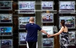 Люди изучают витрину офиса по продаже жилья в Лондоне 22 августа 2016 года. Мэр Лондона Садик Хан пообещал расследовать вопрос владения иностранцами недвижимостью в британской столице, которое повлекло за собой рост стоимости жилья, сообщила газета Guardian в четверг. REUTERS/Peter Nicholls/File Photo