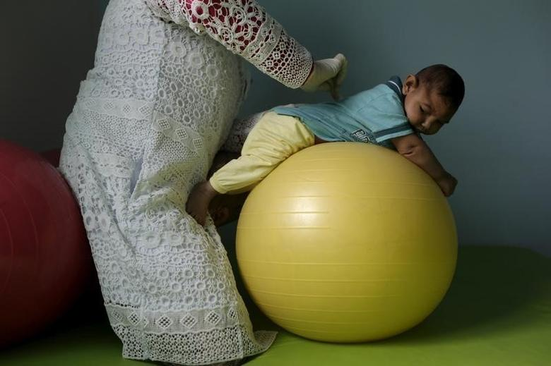 Physiotherapist Jeime Lara Leal does exercises with Lucas, 4-months old, who is Miriam Araujo's second child and born with microcephaly in Pedro I hospital in Campina Grande, Brazil , February 17, 2016. REUTERS/Ricardo Moraes/File Photo