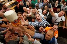 Visitors reach for the one of the first mugs of beer during the opening day of the 183rd Oktoberfest in Munich, Germany, September 17, 2016. REUTERS/Michaela Rehle/File Photo