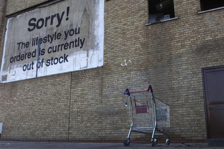 A new work by British artist Banksy, in the form of a billboard, adorns a wall near the Canary Wharf financial district in London December 22, 2011.  REUTERS/Finbarr O'Reilly