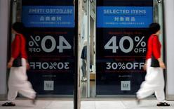 Una mujer saliendo de una tienda en un distrito comercial en Tokio, Japón. 29 de septiembre de 2016. El Índice de Precios al Consumidor (IPC) de Japón cayó en el año a agosto, en su sexto descenso sucesivo, lo que mantuvo la presión sobre el Banco de Japón para que adopte una política monetaria más expansiva mientras busca alcanzar su meta de inflación de un 2 por ciento más rápido. REUTERS/Toru Hanai