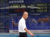 Un hombre camina delante de una pantalla que muestra información bursátil, afuera de una correduría en Tokio, Japón. 9 de septiembre de 2016. Las bolsas de Asia cedían el viernes en medio de la inquietud sobre la salud de Deutsche Bank y los precios del petróleo se alejaban desde unos máximos en un mes por el escepticismo sobre el nuevo plan de la OPEP para reducir su bombeo. REUTERS/Kim Kyung-Hoon