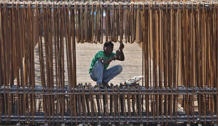 A labourer works at the construction site of a flyover on the outskirts of the western Indian city of Ahmedabad September 28, 2012. REUTERS/Amit Dave/Files