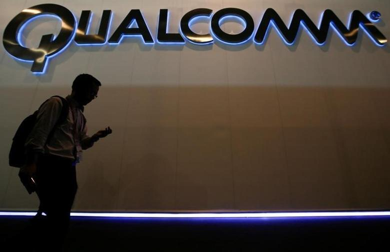 A man walks past Qualcomm stand while attending the Mobile World Congress in Barcelona March 3, 2015.    REUTERS/Albert Gea/File Photo