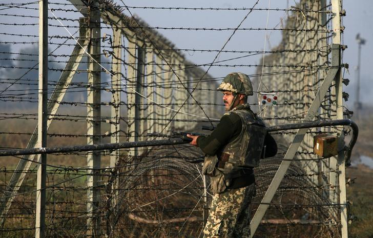 An Indian Border Security Force (BSF) soldier patrols near the fenced border with Pakistan in Suchetgarh, southwest of Jammu January 11, 2013. REUTERS/Mukesh Gupta/Files