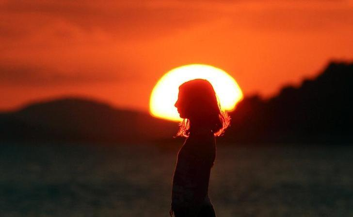 A girl walks along the beach during sunset in the Adriatic village of Sparadici, near the port of Sibenik, Croatia August 14, 2006. REUTERS/Nikola Solic