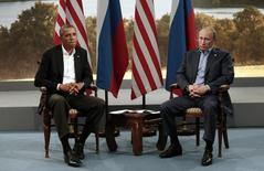 Президент США Барак Обама (слева) и российский лидер Владимир Путин на саммите G8 в  Эннискиллене, Северная Ирландия, 17 июля 2013 года. США объявили в понедельник о приостановке переговоров с Россией об урегулировании сирийского конфликта и обвинили Москву в невыполнении обязательств, принятых в рамках соглашения о режиме прекращения огня.  REUTERS/Kevin Lamarque