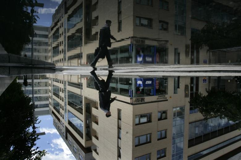A businessman avoids puddles at the International Financial Services Centre - the business district of Dublin May 27, 2007. REUTERS/Luke MacGregor