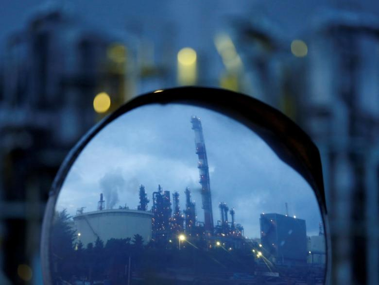 Chimneys of a factory are reflected in a traffic mirror at the Keihin industrial zone in Kawasaki, south of Tokyo, Japan, August 18, 2016. REUTERS/Kim Kyung-Hoon/File photo