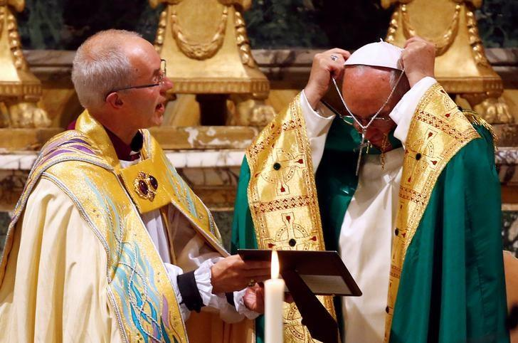 Pope Francis (R) removes a crucifix next to Archbishop of Canterbury Justin Welby at the end of vespers prayers at the monastery church of San Gregorio al Celio in Rome, Italy, October 5, 2016. REUTERS/Tony Gentile