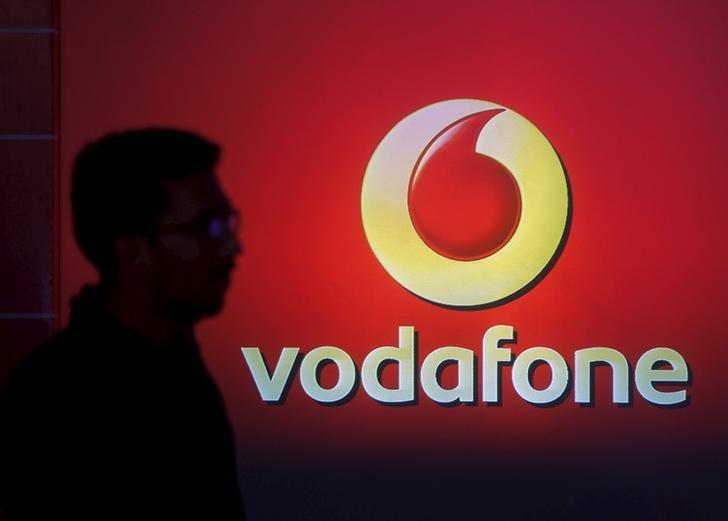A man casts a silhouette onto an electronic screen displaying a Vodafone logo, in Mumbai, India, in this file photograph dated November 10, 2015. REUTERS/Shailesh Andrade/files