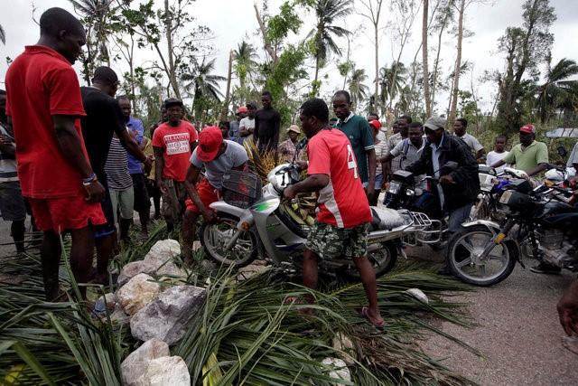 A man pushes his motorbike through a barricade set up on the road to protest against the lack of assistance after Hurricane Matthew in Cavaillon, Haiti, October 6, 2016. REUTERS/Andres Martinez Casares