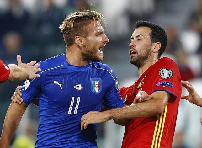 10月6日、サッカーのW杯ロシア大会予選、欧州予選G組のイタリア─スペインは1─1の引き分けに終わった。写真はイタリアのチーロ・インモビレ(左)とスペインのセルヒオ・ブスケツ(2016年 ロイター/Stefano Rellandini)