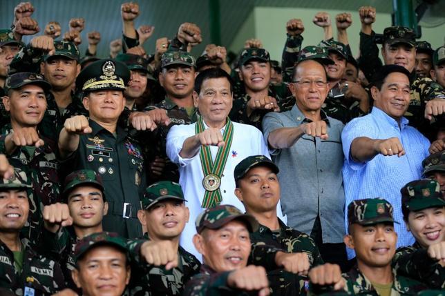 10月7日、フィリピンのロレンザーナ国防相は、同国軍は米軍の支援がなくても存続できるとの見方を示した。写真はドゥテルテ大統領(中央)とフィリピン軍兵士。フィリピンの首都マニラで4日撮影(2016年 ロイター/Romeo Ranoco)