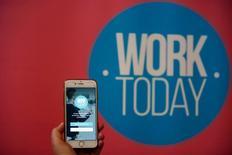 La pequeña 'start-up' de Marta Romero está contratando gente, y no sólo es su plantilla la que está creciendo: también está tratando de encontrar empleo para 4,6 millones de españoles en paro. En la imagen, Marta Romero, CEO y cofundadora de WorkToday, sujeta un iPhone que muestra la página de bienvenida de su aplicación en Madrid, 6 de octubre de 2016. REUTERS/Sergio Pérez