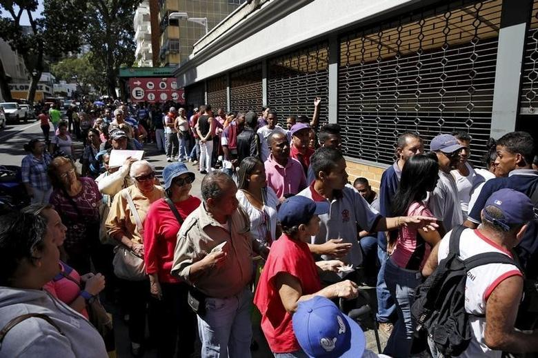 People line up to try to buy corn flour and rice, outside a supermarket in Caracas January 16, 2016.  REUTERS/Carlos Garcia Rawlins