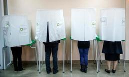 Люди около урн для бюллетеней на избирательном участке в Тбилиси 8 октября 2016 года. В Грузии в субботу проходят парламентские выборы, экзамен для партии власти и тест на стабильность в бывшей советской республике. REUTERS/David Mdzinarishvili
