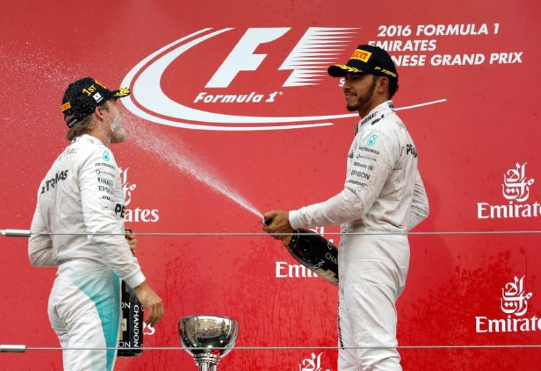 Formula One - Japanese Grand Prix - Suzuka Circuit, Japan- 9/10/16. Mercedes' drivers Nico Rosberg of Germany and Lewis Hamilton of Britain celebrate with champagne during an awarding ceremony at the race. REUTERS/Toru Hanai