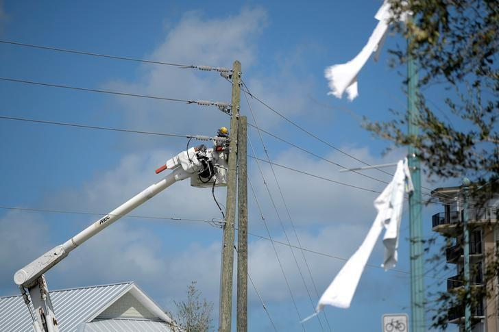 A utility worker repairs a power line in the aftermath of Hurricane Matthew in New Smyrna Beach, Florida, U.S. October 9, 2016.  REUTERS/Phelan Ebenhack