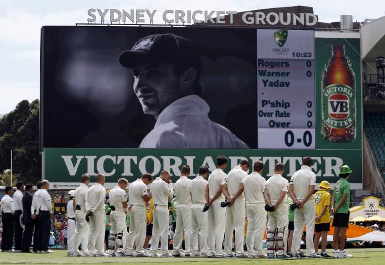 Australia's Nathan Lyon (C) reacts with team mates and officials during a ceremony in memory of team mate Phillip Hughes before the start of the first day's play in the fourth test against India at the Sydney Cricket Ground (SCG) January 6, 2015. REUTERS/David Gray