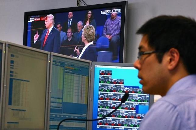 10月9日、米大統領選の候補者による第2回討論会が行われたが、米株先物は討論会の間、ほとんど動かず、市場が引き続き、民主党候補のクリントン氏が共和党のトランプ氏に勝利すると予想していることが示された。写真は討論会を見ながら働くトレーダー、シドニーで10日撮影(2016年 ロイター/David Gray)