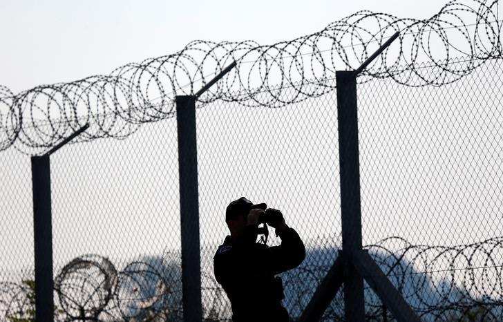 A Polish policeman patrols at the Hungary and Serbia border fence near the village of Asotthalom, Hungary, October 2, 2016 as Hungarians vote in a referendum on the European Union's migrant quotas. REUTERS/Laszlo Balogh