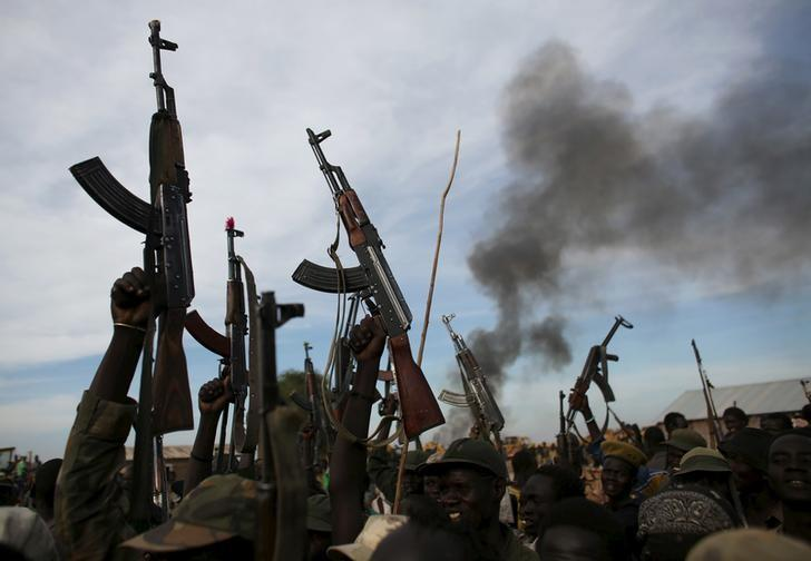 Rebel fighters hold up their rifles as they walk in front of a bushfire in a rebel-controlled territory in Upper Nile State, South Sudan February 13, 2014.     REUTERS/Goran Tomasevic