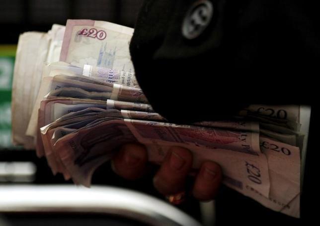 10月11日、ポンドがドルに対して1.22ドル付近まで下落した。写真は現金を手にする人。イングランド西部で2009年3月撮影(2016年 ロイター/Dylan Martinez)