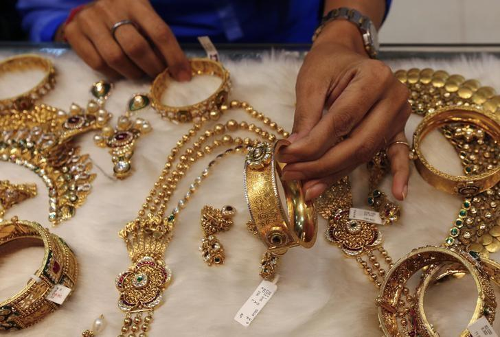 A woman looks at a gold bangle inside a jewellery showroom at a market in Mumbai January 15, 2015.  REUTERS/Shailesh Andrade