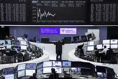Traders work at their desks in front of the German share price index, DAX board, at the stock exchange in Frankfurt, Germany, October 12, 2016. REUTERS/Staff/Remote