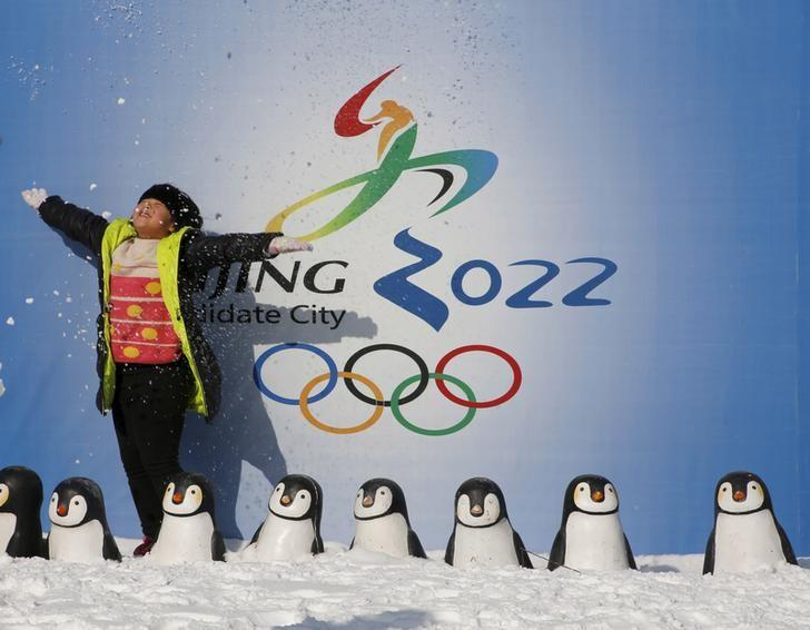 A girl throws snow into the air as she poses for her souvenir picture in front of a board celebrating Beijing as the host of the 2022 Winter Olympics, during the Ice and Snow carnival at Taoranting park in Beijing, China, January 25, 2016.REUTERS/Kim Kyung-Hoon/files