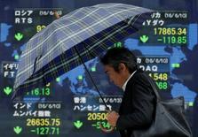 Un peatón pasa delante de una pantalla que muestra información bursátil, afuera de una correduría en Tokio, Japón. 13 de junio de 2016. Las bolsas de Asia tocaron el miércoles unos mínimos en tres semanas luego de un inicio decepcionante de la temporada de resultados corporativos, y el dólar repuntaba por un aumento de las expectativas de una subida de las tasas de interés de Estados Unidos en diciembre. REUTERS/Issei Kato