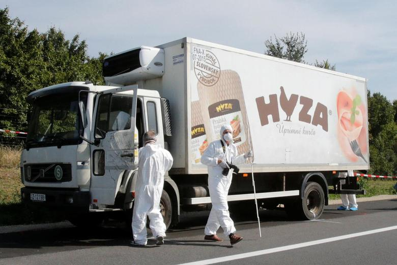 Forensic police officers inspect a parked truck in which up to 50 migrants were found dead, on a motorway near Parndorf, Austria August 27, 2015.   REUTERS/Heinz-Peter Bader