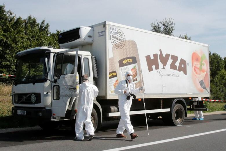 Forensic police officers inspect a parked truck in which up to 50 migrants were found dead, on a motorway near Parndorf, Austria August 27, 2015.   REUTERS/Heinz-Peter Bader/File photo