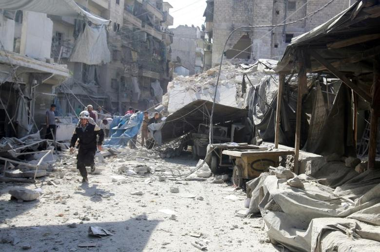 A civil defence member runs at a market hit by air strikes in Aleppo's rebel-held al-Fardous district, Syria October 12, 2016. REUTERS/Abdalrhman Ismail