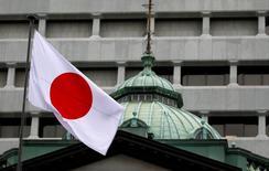 Японский флаг над зданием Банка Японии в Токио. Банк Японии, скорее всего, немного снизит прогноз инфляции на следующий финансовый год в своем квартальном отчете, сообщили источники, знакомые с ситуацией, однако вряд ли в ближайшее время смягчит политику после ее пересмотра в сентябре.  REUTERS/Toru Hanai