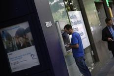 El Ayuntamiento de Madrid dijo el jueves que ha introducido una nueva tasa que deberán pagar los bancos a partir de 2017 por los cajeros automáticos que estén en la vía pública. En la imagen, un hombre utiliza un cajero automático en una sucursal del BBVA en Madrid, el 30 de abril de 2014. REUTERS/Susana Vera