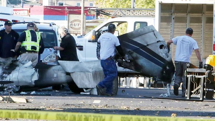 Wreckage is removed from the scene of a twin-engine plane that struck a utility pole and burst into flames in downtown East Hartford, Connecticut U.S., October 12, 2016.  REUTERS/Michelle McLoughlin