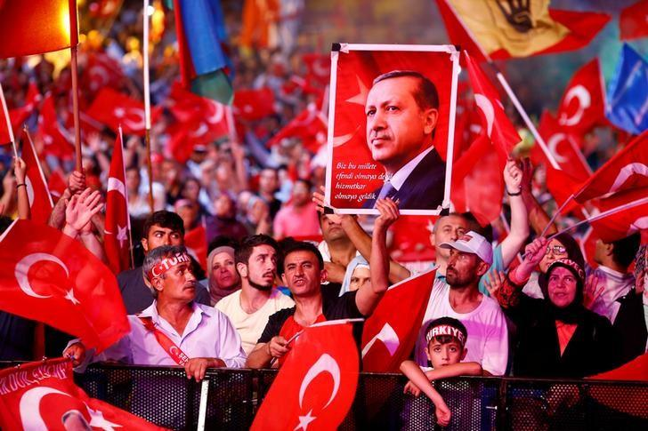Supporters of Turkish President Recep Tayyip Erdogan wave national flags as they listen to him through a giant screen in Istanbul's Taksim Square, Turkey, August 10, 2016. REUTERS/Osman Orsal/File Photo