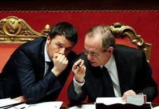 El gabinete del primer ministro italiano, Mateo Renzi, se reunirá el sábado para aprobar el borrador de presupuestos para 2017, con la esperanza de que una modesta reducción en el objetivo de déficit convenza a la Comisión Europea.  En la imagen de archivo, el primer ministro italiano Matteo Renzi (izquierda) habla con el ministro de finanzas Pier Carlo Padoan durante una votación en el Senado en Roma el 24 de febrero de 2014. REUTERS/Remo Casilli/File photo