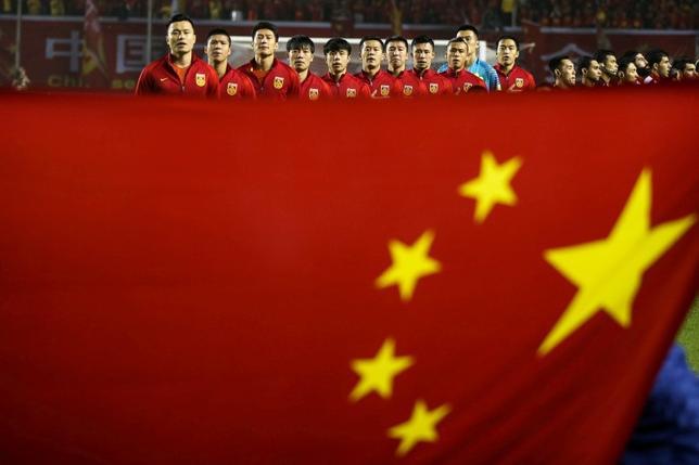 10月14日、中国が掲げる世界のサッカー王国になるという野望は、厳しい現実に直面している。ワールドカップロシア大会のアジア最終予選で中国代表はシリアとウズベキスタンに連敗し、代表監督が辞任。2018年の本大会出場は絶望的な状況だ。写真は6日、中国国旗とシリア戦を控えた中国代表(2016年 ロイター)