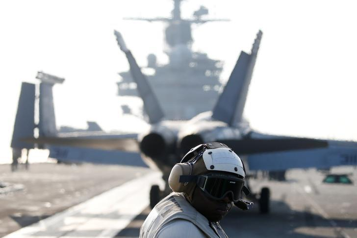 A U.S. Navy crew member looks at a F/A-18 Super Hornet fighter as it prepares for take off from the USS Ronald Reagan, a Nimitz-class nuclear-powered super carrier, during a joint naval drill between South Korea and the U.S., in the West Sea, South Korea, October 14, 2016.  REUTERS/Kim Hong-Ji