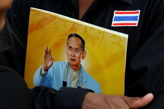 A mourner holds a portrait of the late King Bhumibol Adulyadej as another waits to pay respects to him outside the Grand Palace in Bangkok, in Bangkok, Thailand, October 17, 2016. REUTERS/Chaiwat Subprasom